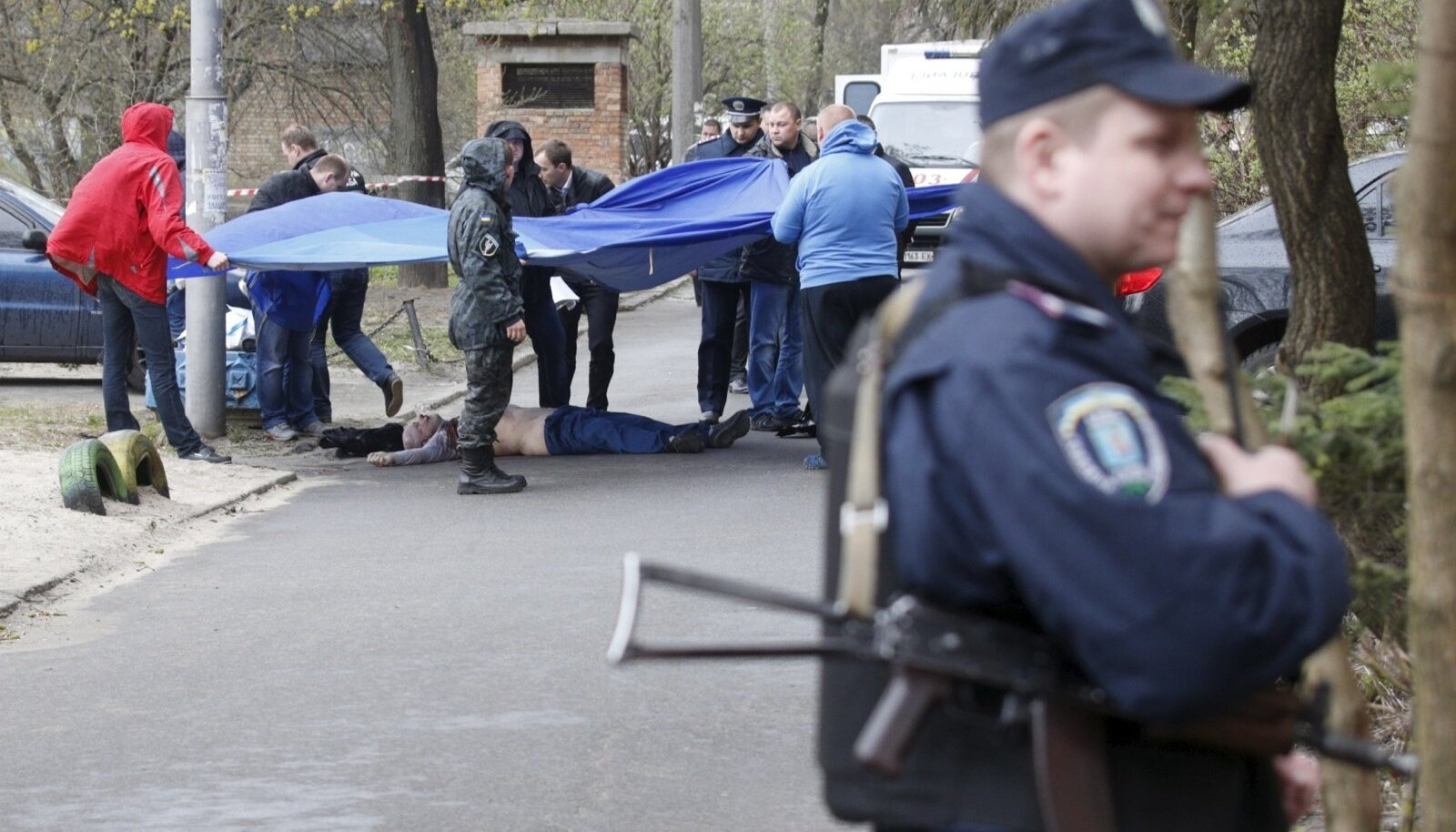 Investigators work near the body of journalist Oles Buzina in Kiev