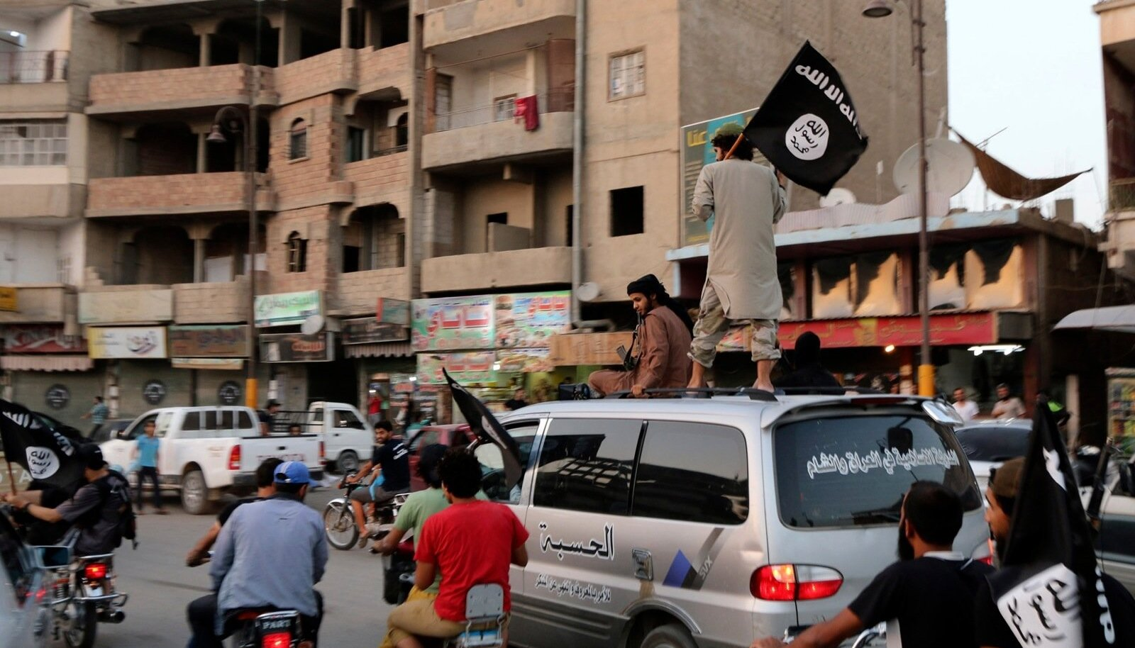 Members loyal to the ISIL wave ISIL flags as they drive around Raqqa