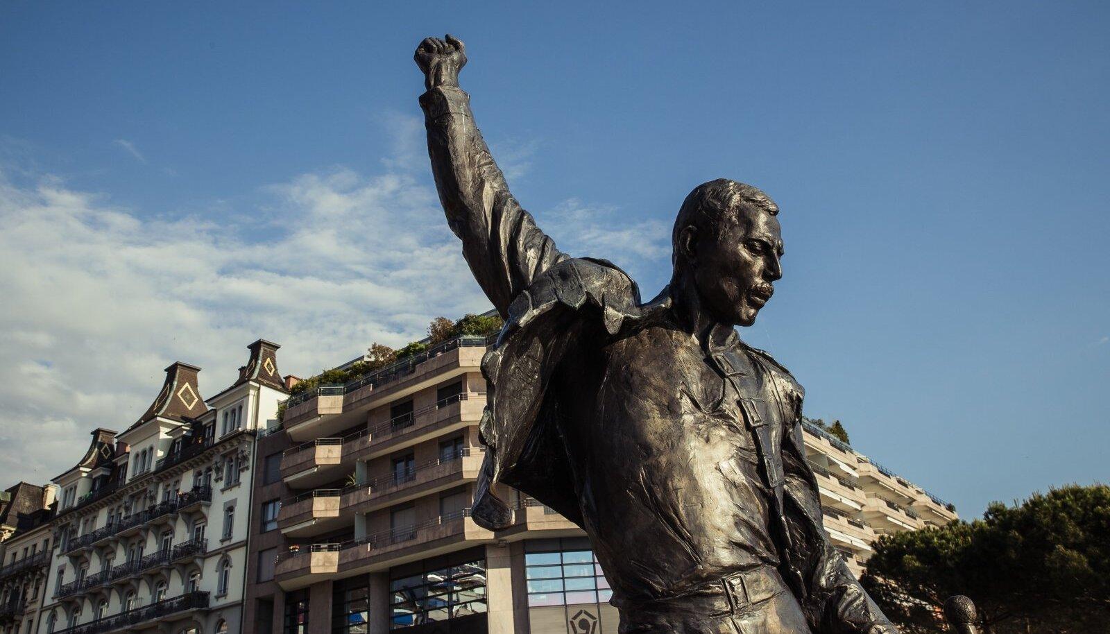 Freddie Mercury monument Genfi järve kaldal. Lauljat on kujutatud talle omases poosis: rusikas taeva poole sirutatud, pilk jumaldavate fännide silmadesse suunatud.