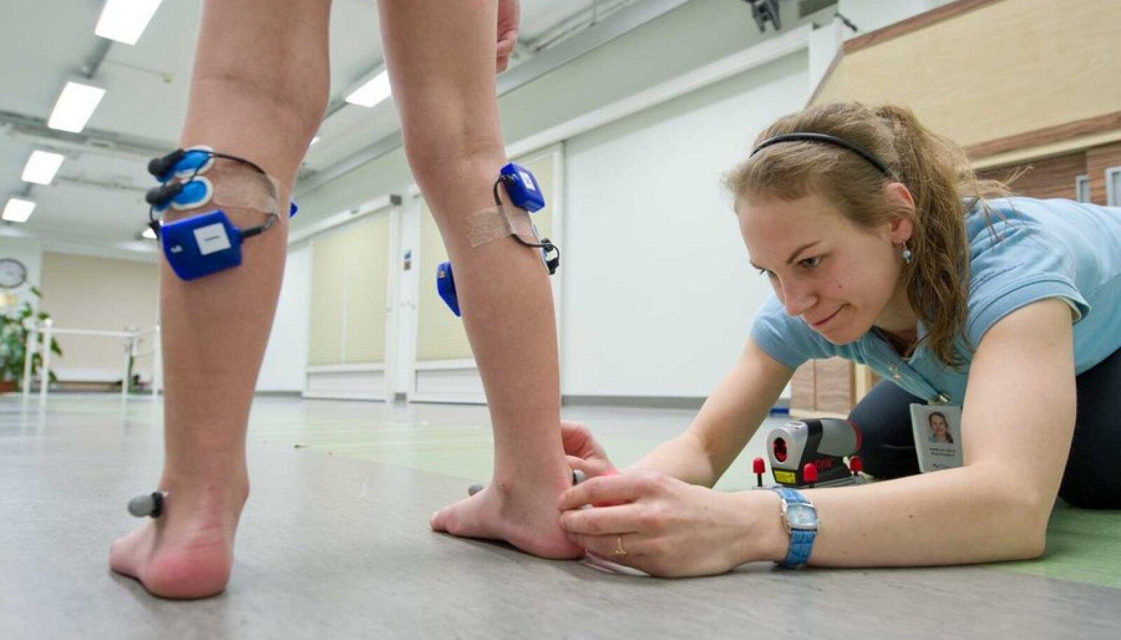 Füsioterapeut Mari Alvelal kulub ligi tund, et kinnitada Toomase jalgadele kõik kõnnianalüüsiks vajalikud antennid ja andurid. (Foto: Rauno Volmar)