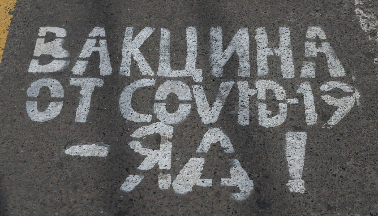 """""""Koroonavaktsiin on mürk!"""" kuulutab kiri asfaldil. Täpsemalt on Vene propaganda arvates mürk läänes toodetud vaktsiin."""