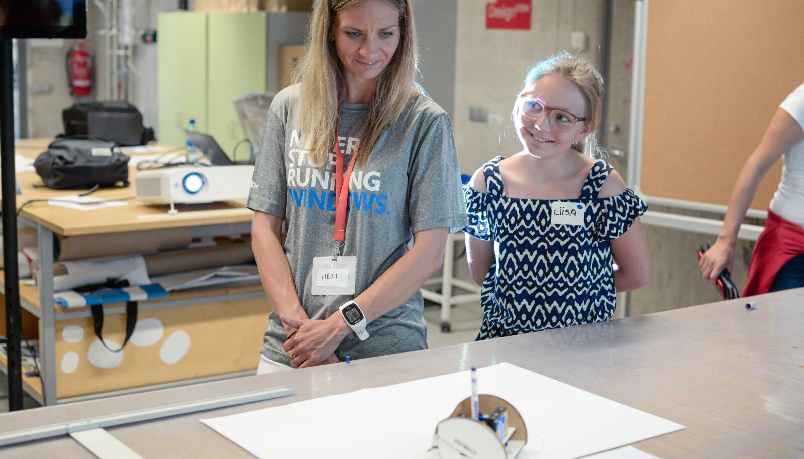 Juhendaja Heli Sepping ja Liisa joonistava Miroboti robotiga.