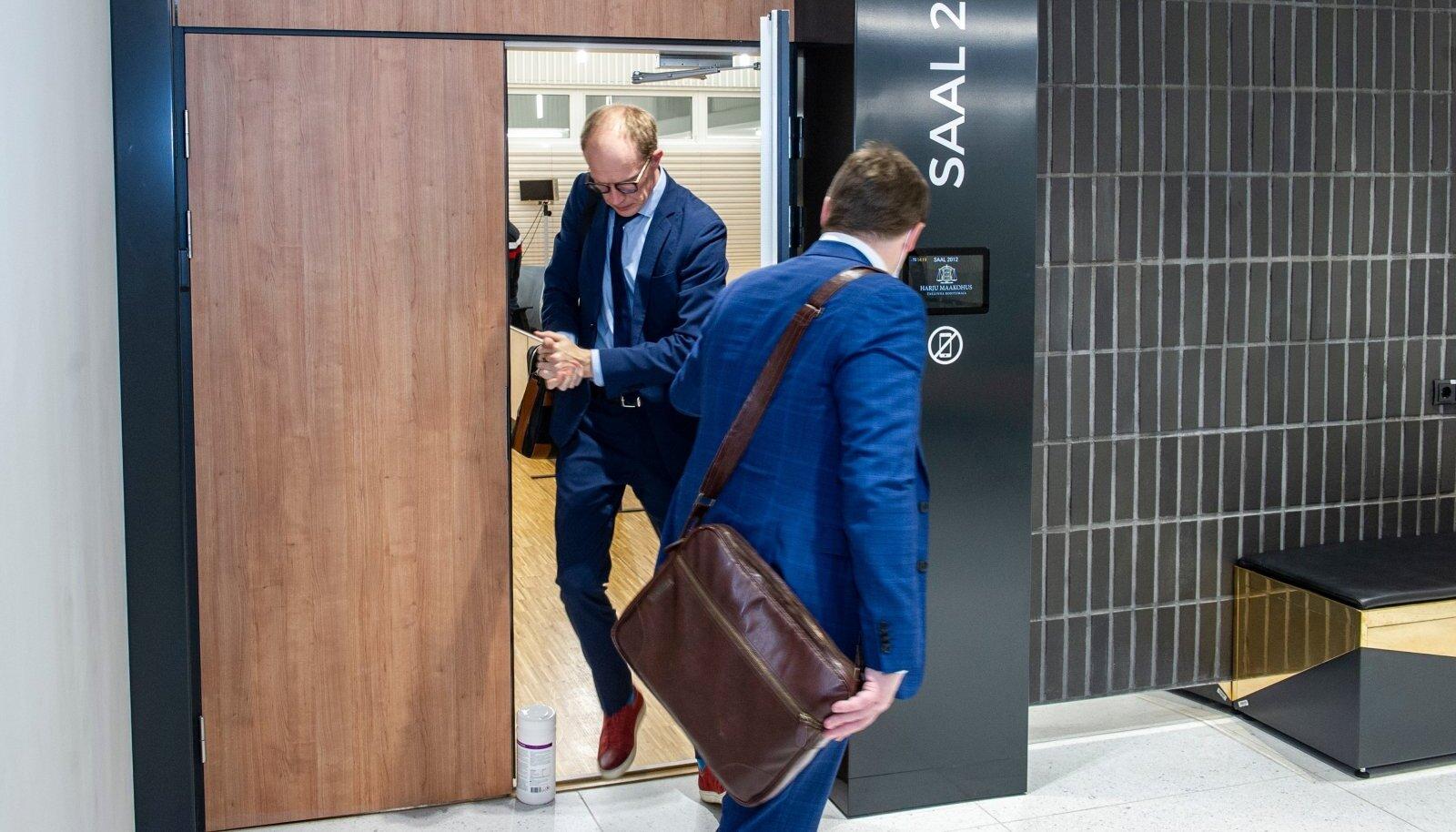 ODAV JA TÕHUS: Advokaat Tanel Mällas (seljaga) vaatab, et advokatuuri esimees Jaanus Tehver ei komistaks kohtusaalist väljudes plastpurgi otsa. Purki kasutatakse Harju maakohtu suurima istungisaali nr 2012 ukse praokil hoidmiseks, et tagada istungite ajal koroonaviiruse ohtu vähendav õhuvahetus. Kuigi 2018. aastal avatud kohtuhoone ehitus maksis riigile 35 miljonit eurot, ei saa ilma purgita õigust mõista.