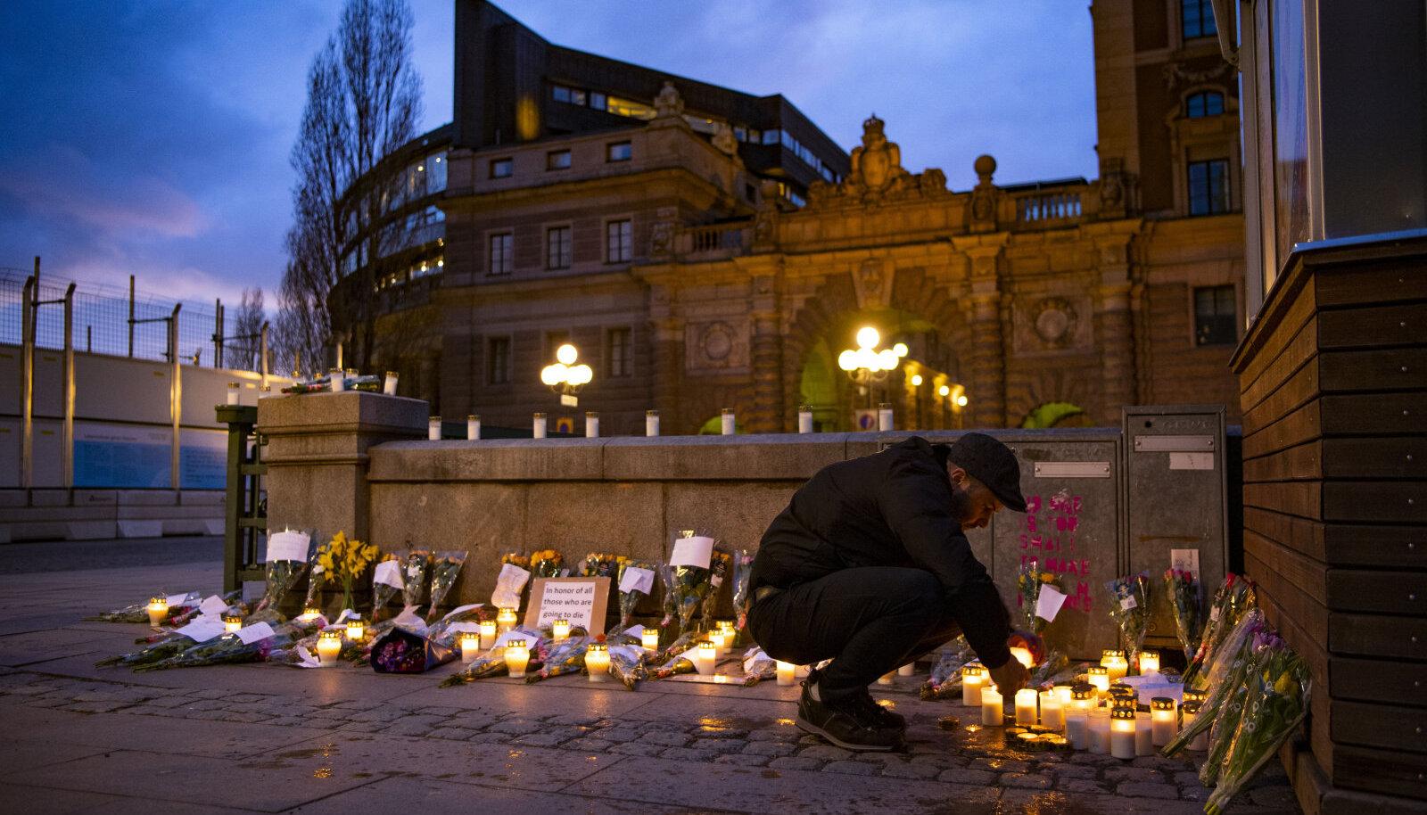 Rootslased viivad parlamendihoone ette küünlaid ja lilli koroonaviiruse ohvritele.