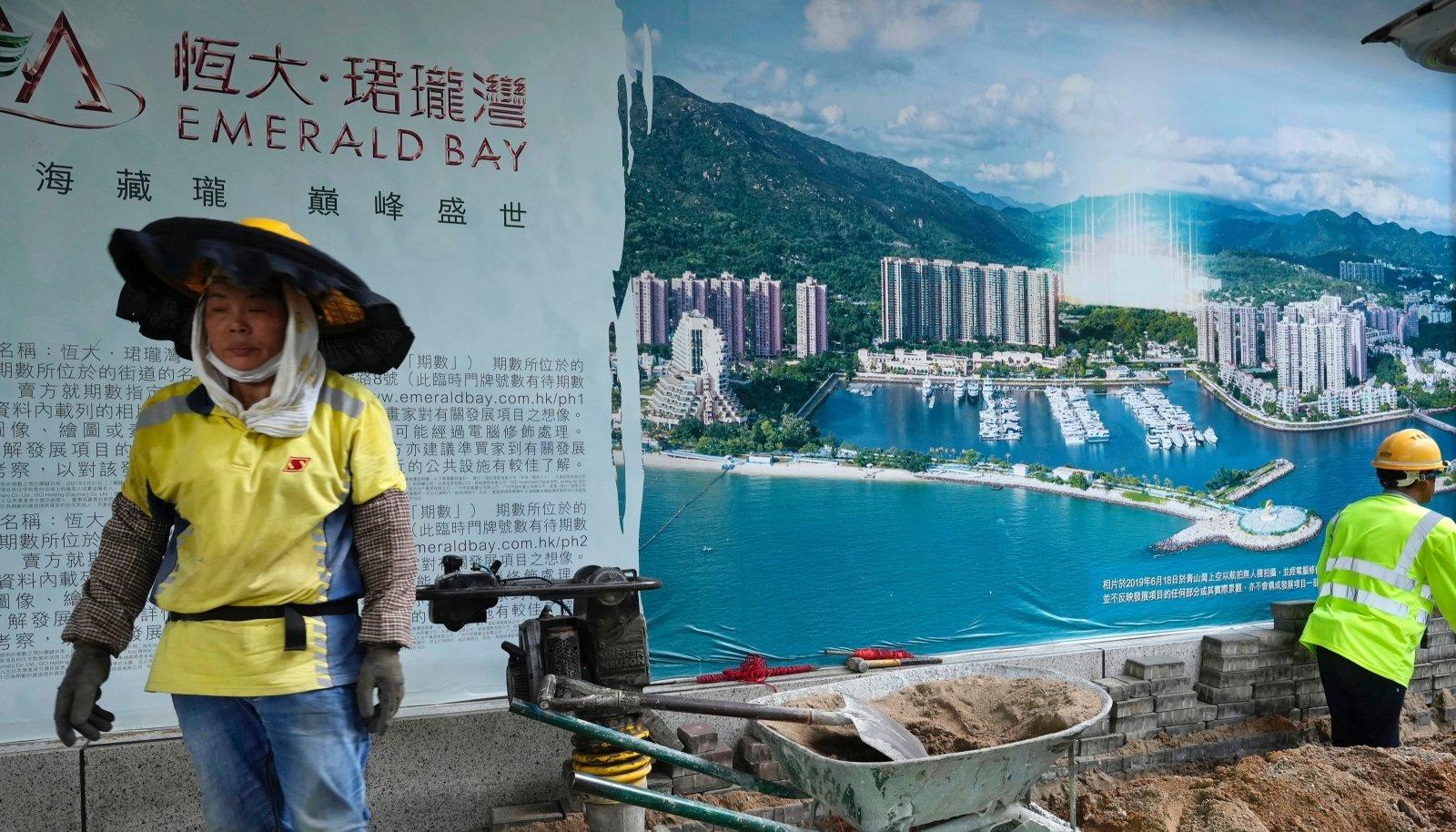 Töölised eile Evergrande'i peakontorit ehtiva järjekordse arendusprojekti reklaami taustal. Lausa 20% Hiina linnade tööjõudu tegutseb ehituses.