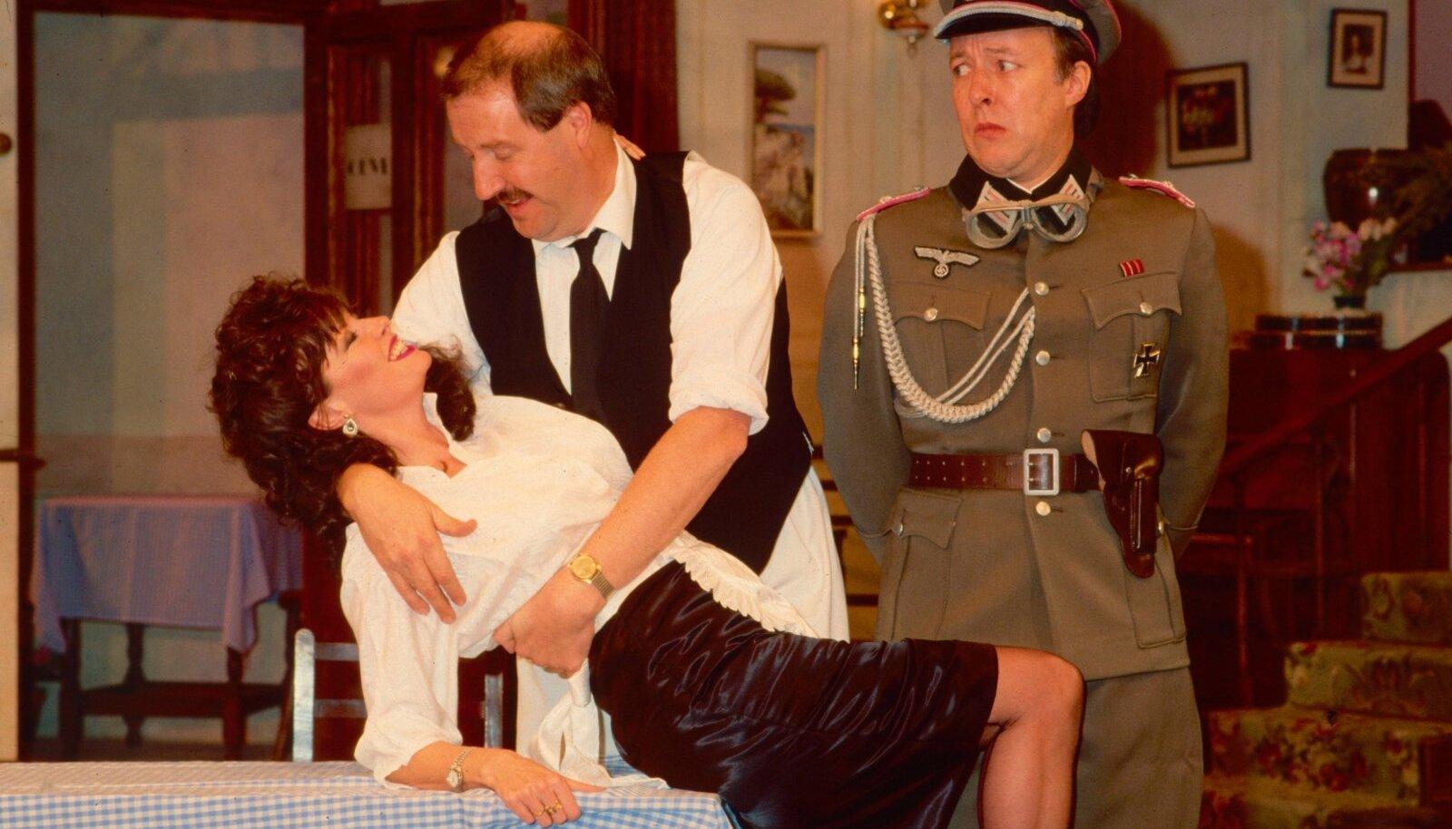 Prantsuse kohvikuomanik René (Gorden Kaye, keskel), tema armuke, ettekandja Yvette (Vicki Michelle) ja saksa leitnant Hubert Gruber (Guy Siner) 1980-ndate keskel