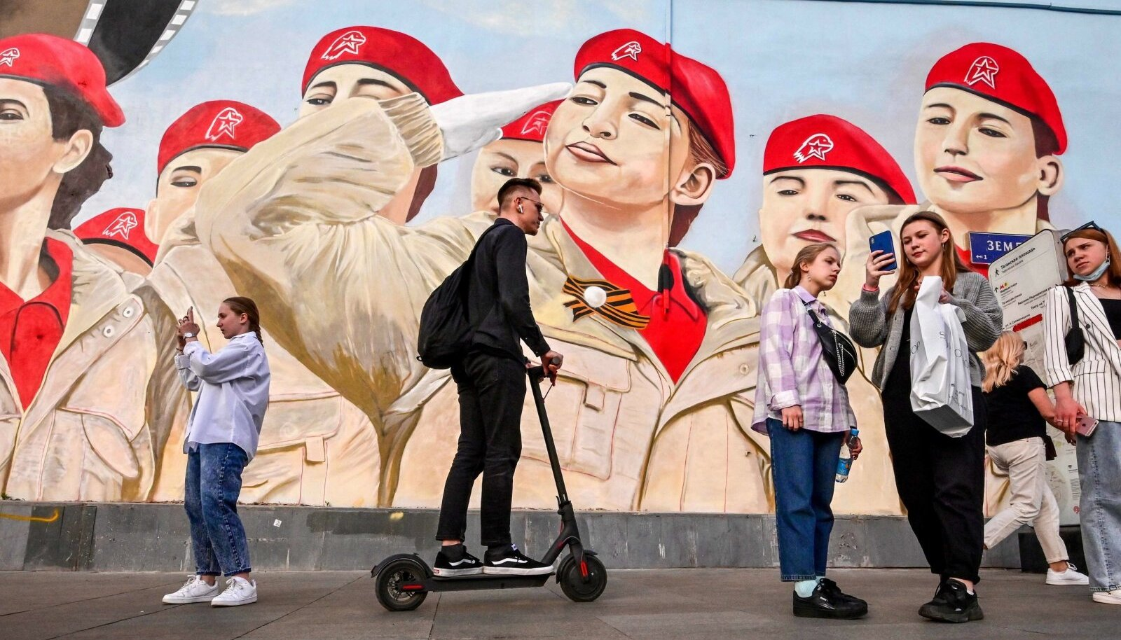 Kremli üks suurimaid muresid enne sügisesi valimisi on küsimus, kuidas saada inimesed hääletama. Pildil on Moskva elanikud sõjalis-patriootlikku noorteliikumist Junarmija kujutava seinamaali taustal.