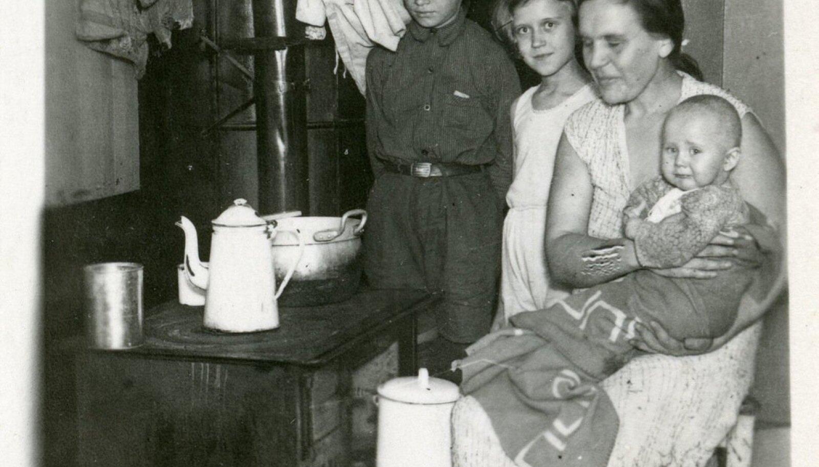 Töölisnaine koos oma lastega pildistatud köök-toas.
