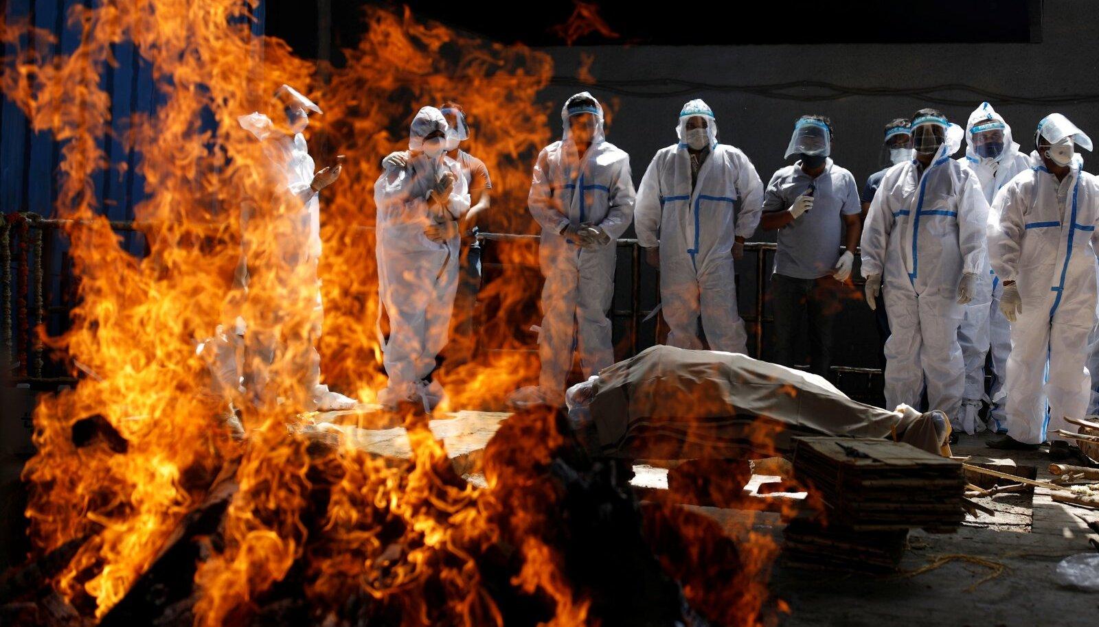 MATUSETALITUS INDIAS AASTAL 2021: Kaitseülikondades sugulased on kogunenud koroonaviirusesse surnud lähedase matustele.