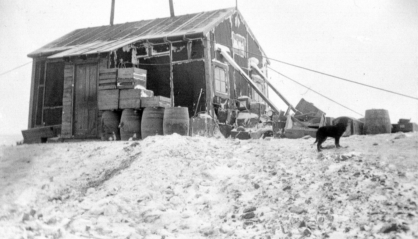 Rootslaste uurimisjaam esimese ekspeditsiooni ajal 1901. aastal. Tünnid ja kastid varjavad maja tugeva tuule eest.