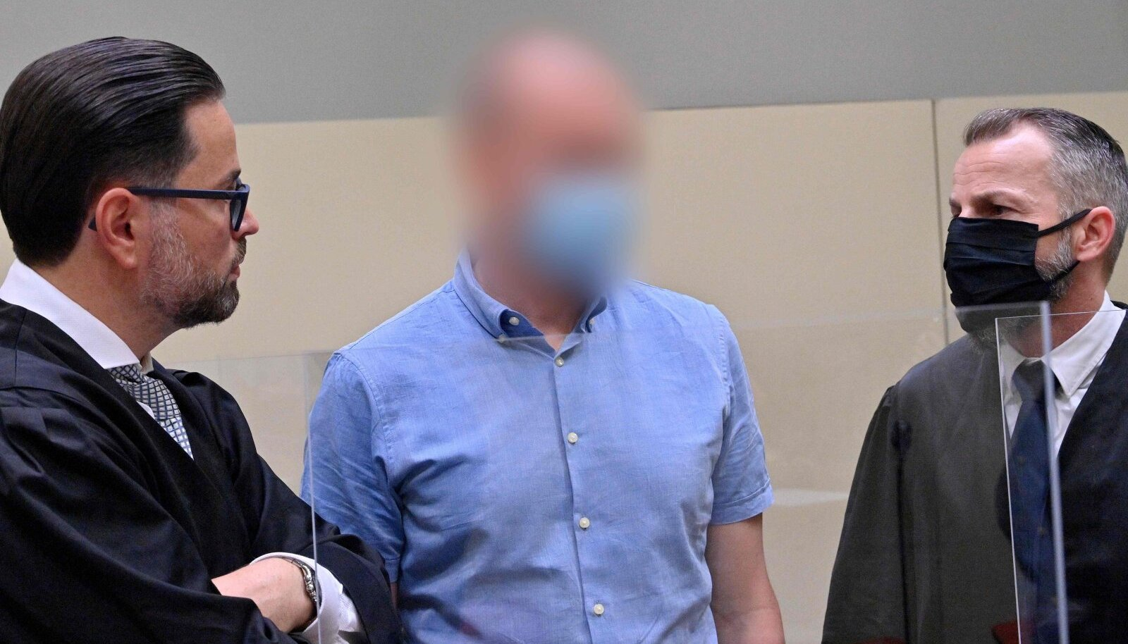 Dopinguarst Mark Schmidt kahe advokaadi keskel.