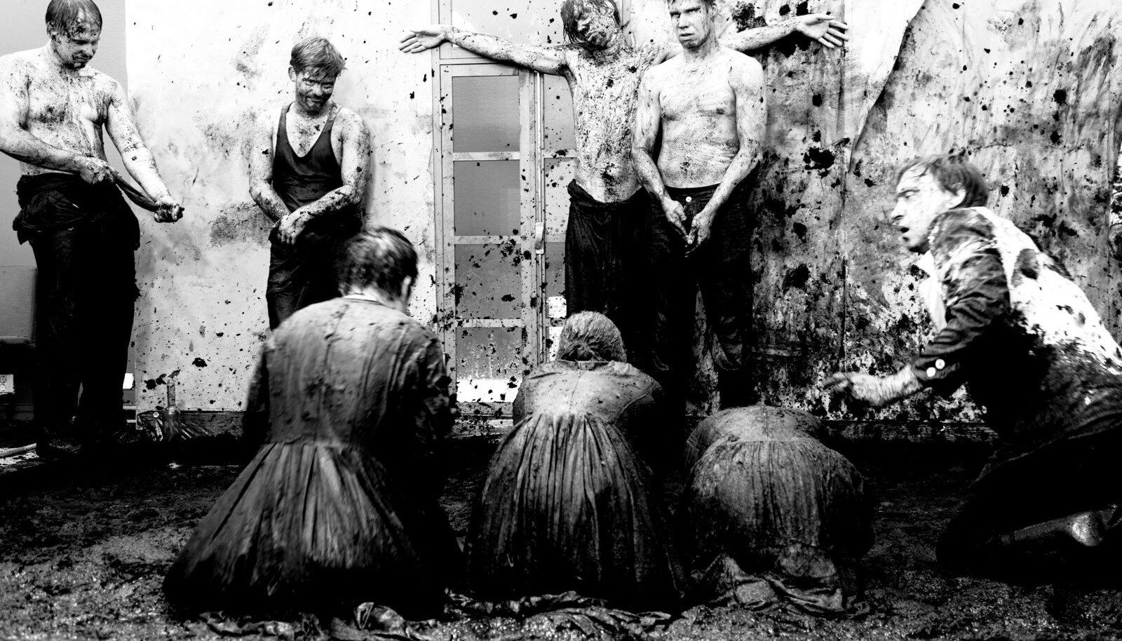 """▲ """"Praise the Lord!"""" hüüab mass NO teatri lavale ehitatud tsivilisatsiooni mülkas, nii eluski. On XXI sajand. Vahemaad on jäänud väiksemaks ning kusagil siinsamas raiutakse maha päid ja loobitakse naisi kividega surnuks. Just praegu sünnib üks eesti laps ja just praegu peksab üks jõhkardist mees oma laste ema. Tsiviliseerituse õhuke, õhuke kiht."""