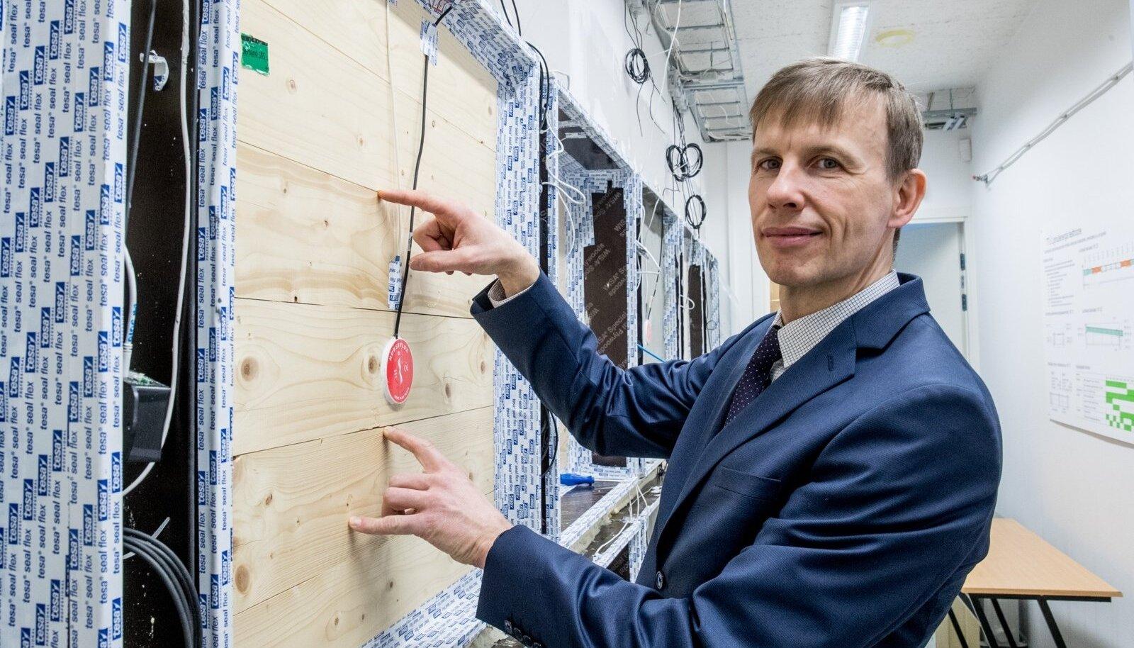 Professor Targo Kalamees näitab liginullenergia katsetamishoones uuritavaid ristkihtpuit-seinaelemente, millele on andmete kogumiseks paigaldatud kokku sada sensorit.