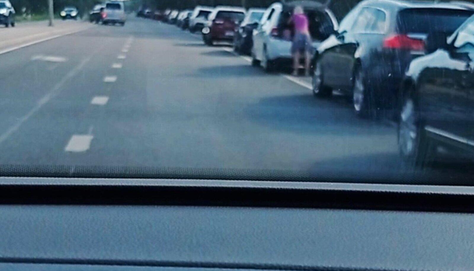 Pargitud autode vahel sagivad inimesed.