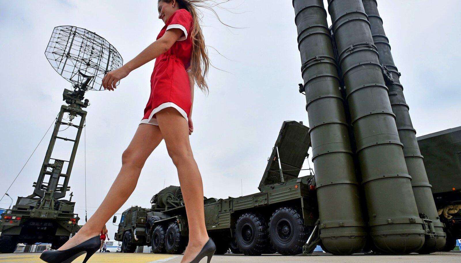 TURUNDAMINE: Nagu pesumasinaid või autosid, müüakse ka relvi naise keha abil. Vene relvamess Oboronexpo 2014. Jalgade taustaks on õhutõrjekompleks S-400. Seesama, mille Türgi äsja Venemaalt ostis, sattudes vastuollu ülejäänud NATO riikidega. Türgi president ei lasknud end sellest häirida.