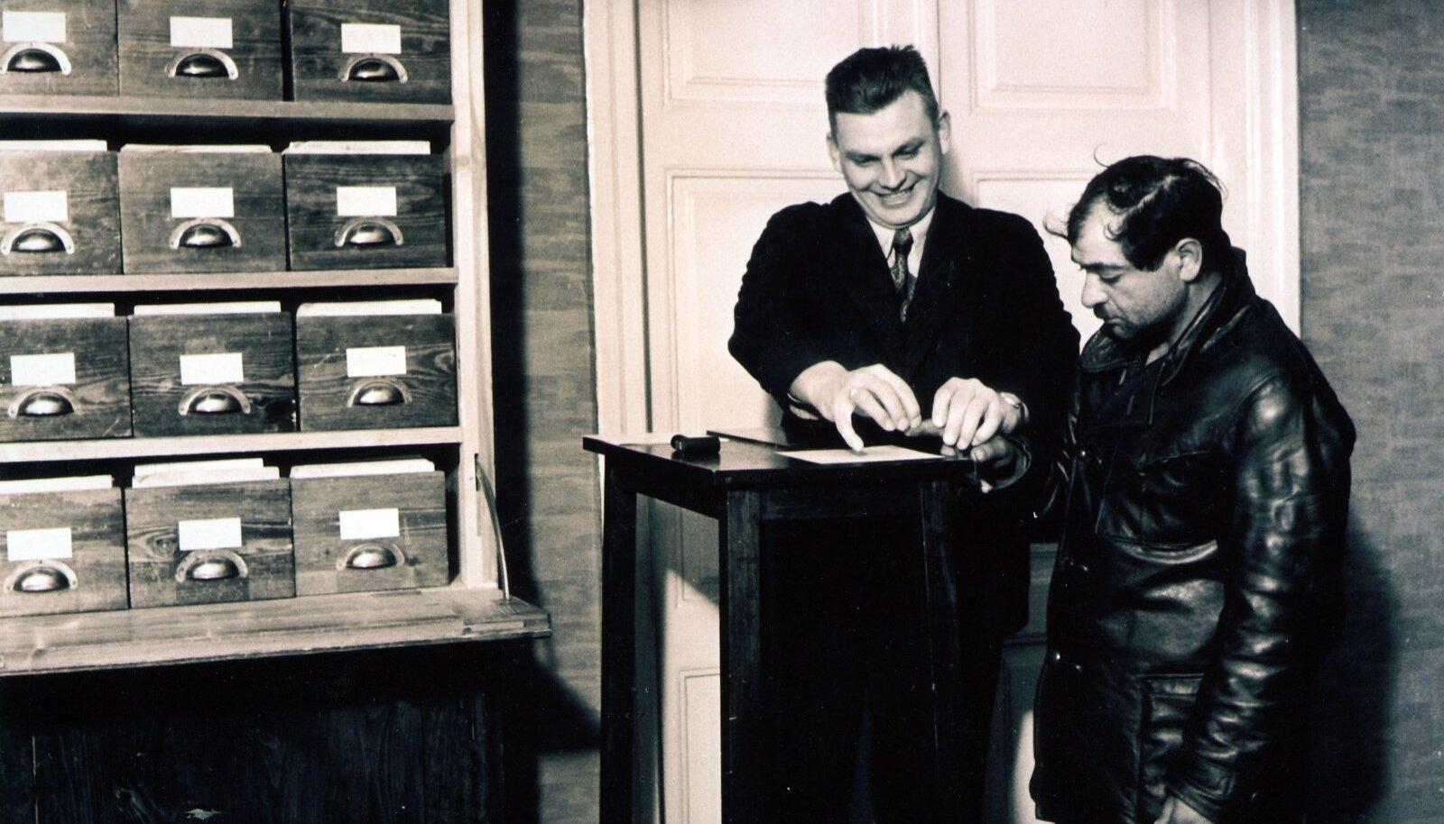 JÄI VAHELE: Tallinn-Harju kriminaalpolitsei töötaja võtab kurjategijalt kartoteegi jaoks sõrmejälje. Foto aastast 1937.