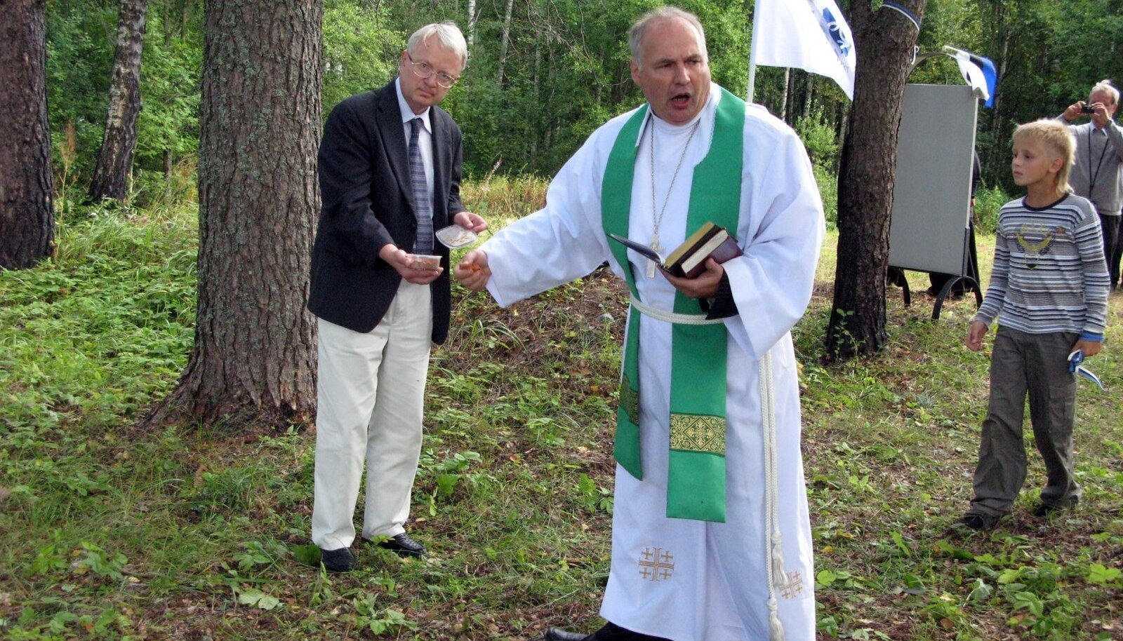 Eestlaste kalmistu Ishutinos, Tveri oblastis. Kalmistul puhkavatele eestlastele tegi pühitsustalituse pastor Eestist Enn Salveste. Peeter Luksep (vasakul) võttis selleks tarbeks Eestist kaasa karbi mullaliivaga.