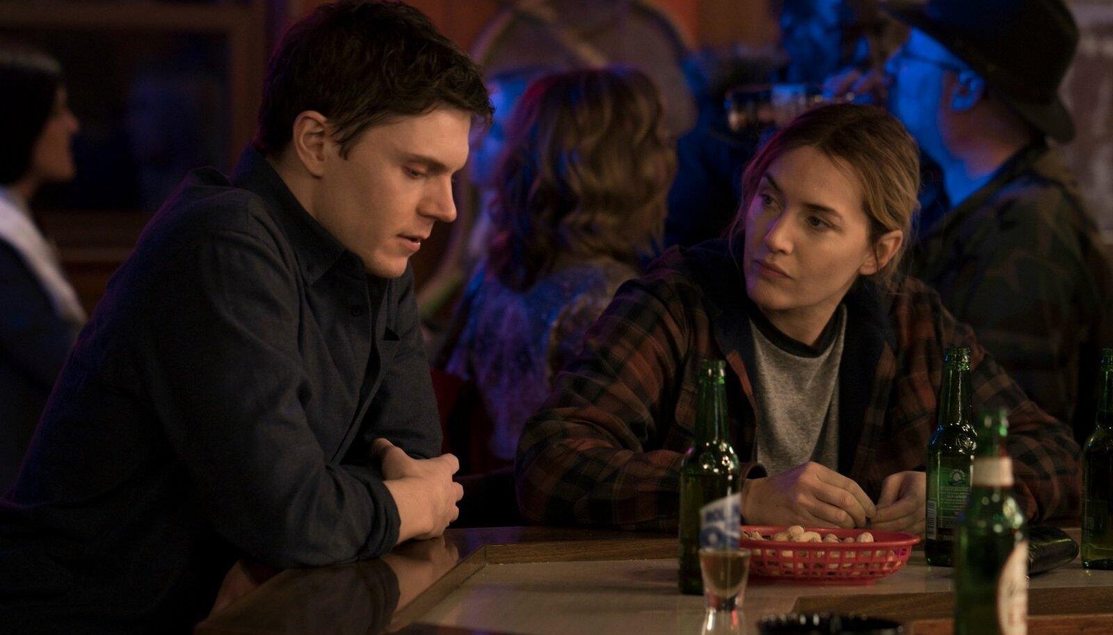 VÄIKELINNA MURED JA RÕÕMUD: Mare (Kate Winslet) ja tema noor kolleeg Colin (Evan Peters) baarileti taga elu- ja tööasju arutamas.