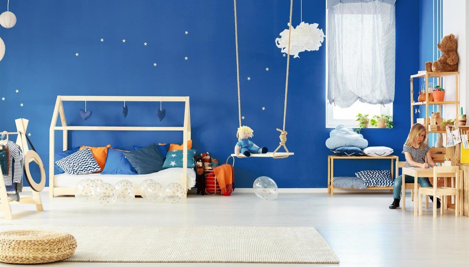 Voodi põrandal, riided lapsele sobivas kõrguses ja taevatähed seinal.