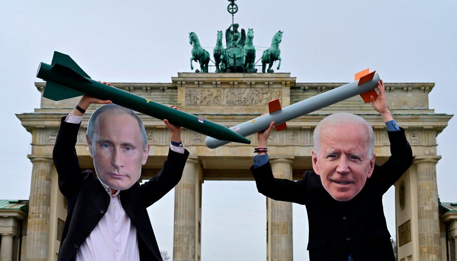 ESKALEERI-DEESKALEERI: Putini ja Bideni maske kandvad rahuaktivistid jaanuaris Berliinis Brandenburgi värava ees.