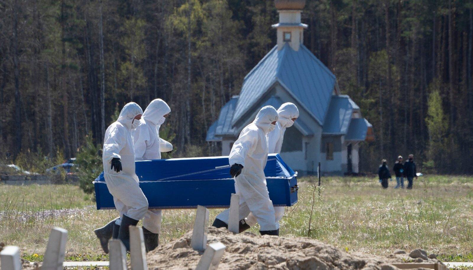VIIRUS MURRAB: Kaitseriietuses surnumatjad tassivad Venemaal Kolpino lähistel COVID-19 ohvriga kirstu.