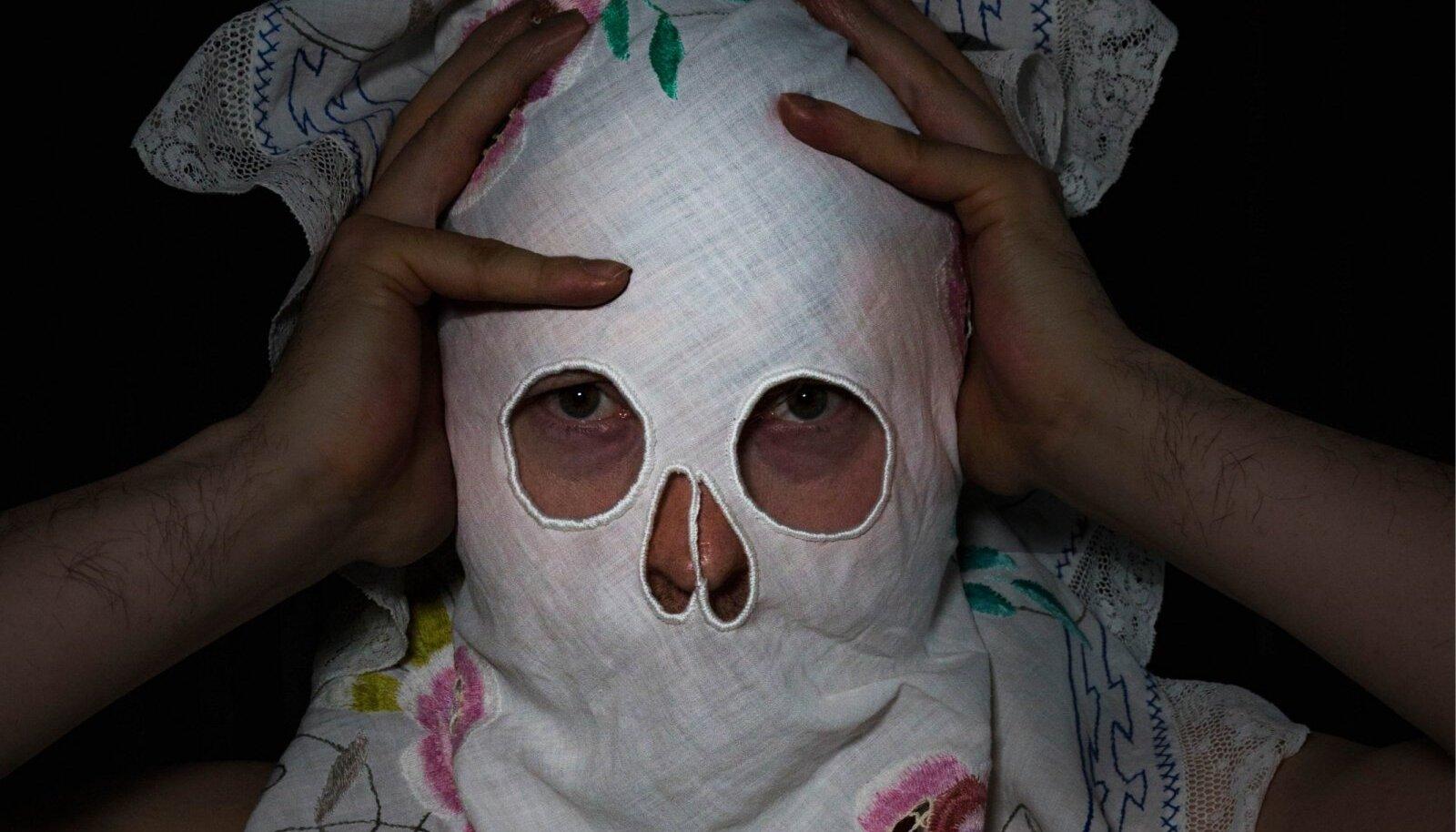 Galerii ülakorrusel on eksponeeritud suured fotod, kus tikitud padjapüüridest-linikutest on saanud maskid, millel kohati kasutatud õudusfilmide motiive.