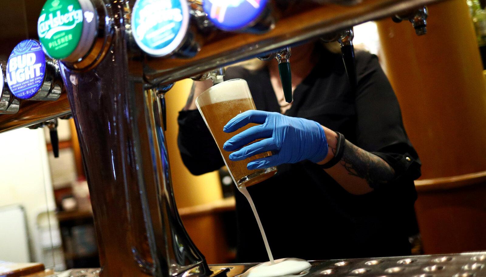 Londoni pubitöötaja juulikuise taasavamise järel õlut valamas