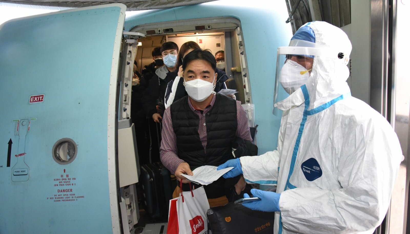TÄIELIK KONTROLL: Reisijad väljuvad meditsiinitöötaja valvsa pilgu all Qingdao lennujaamas lennukist.