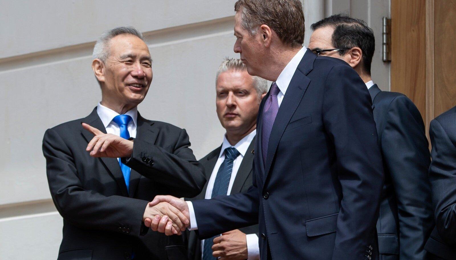 Hiina asepeaminister Liu He (vasakul) surumas reedel USA kaubandusvoliniku Robert Lighthizeri kätt pärast läbirääkimiste ummikusse jooksmist ja enne Washingtonist lahkumist.