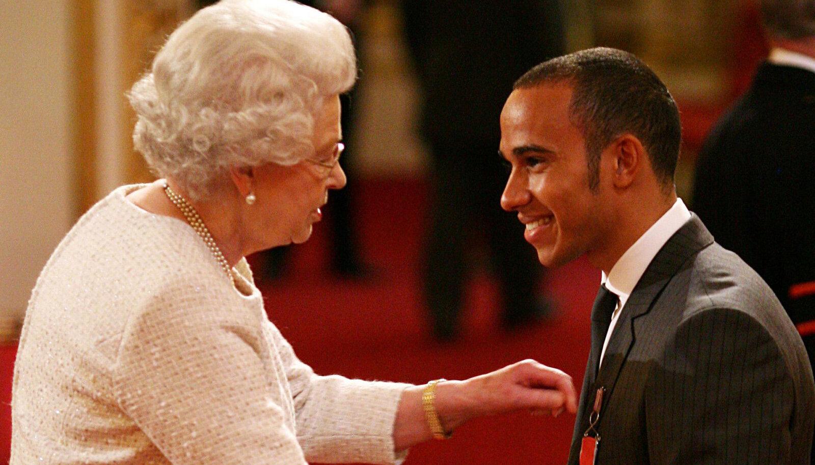 Lewis Hamilton 2009. aastal Elizabeth II-lt Briti impeeriumi ordu medalit saamas.