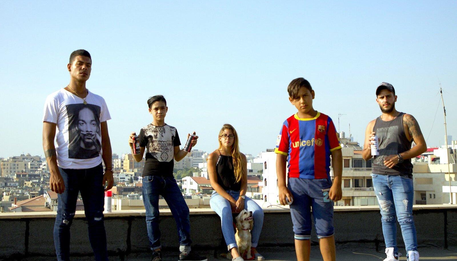 """Kaader filmist """"Tere tulemast Ouzville'i"""". Beiruti lõunaosas asuvat Ouzai linnajagu peetakse ohutsooniks, kus peremehetsevad relvastatud jõugud ja kurjategijad. Vaatamata sellele loodavad noored just kodulinnas oma unistused teoks teha."""