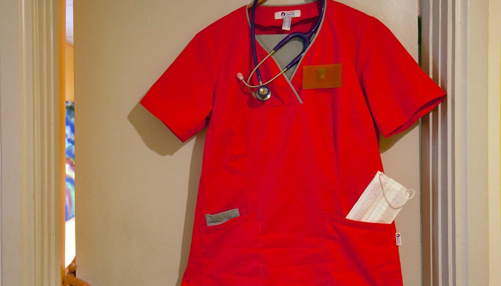 Perearsti riided ja stetoskoop riidepuul