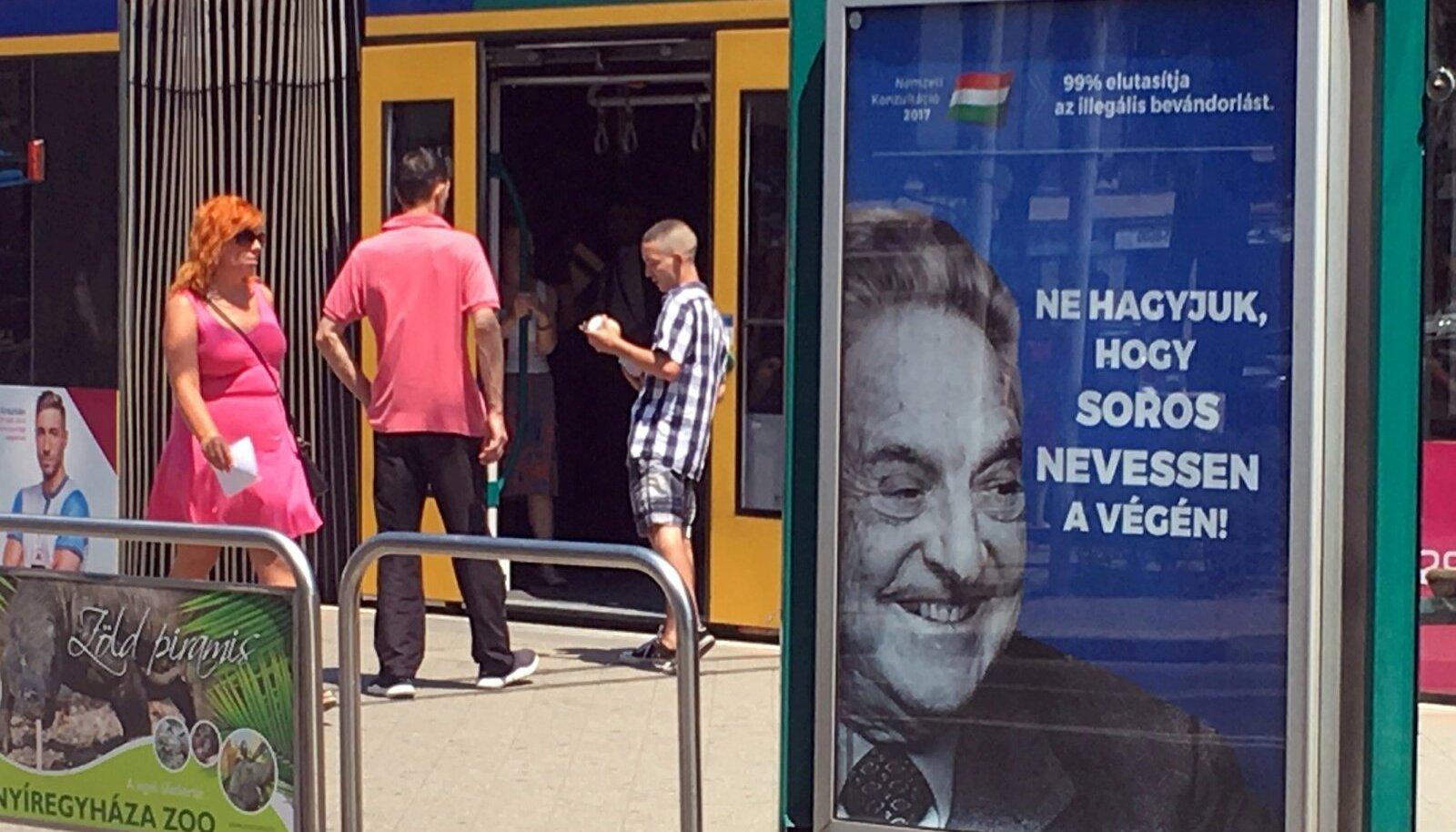 Budapesti trammipeatustes jälgib ungarlasi Sorose saatanlik irve.