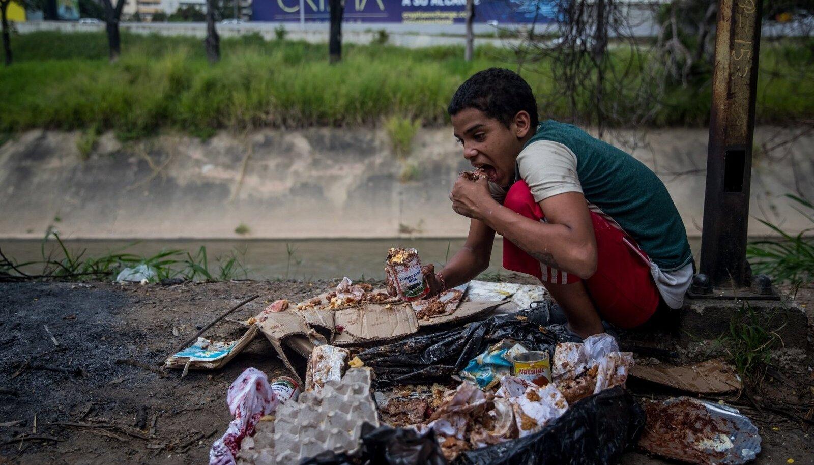 Jesus (16) sööb toitu, mille leidis pagarikoja prügikotist. Pilt on tehtud Venezuela pealinnas Caracases 10. novembril 2018. Raske majandus- ja sotsiaalkriisi tõttu kubisevad Caracase tänavad kodututest lastest.