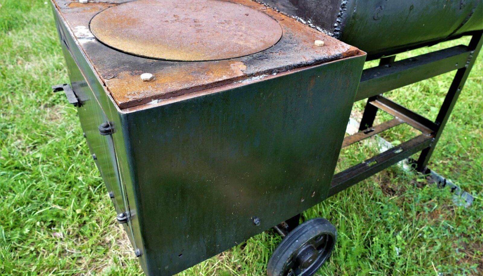 Suitsugrilli küttekolle on kaetud malmist pliidiplaadiga.