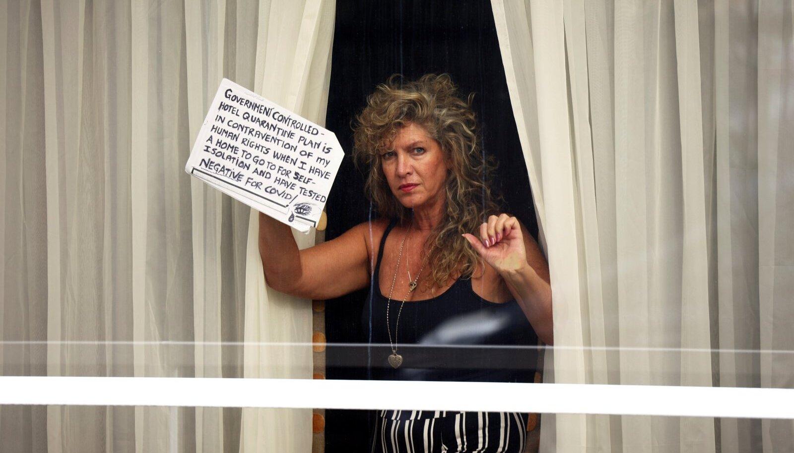"""TAHAN KOJU: Suurbritannias paigutati veebruaris kolmekümnest """"punasesse nimekirja"""" märgitud riigist saabujad kohustuslikku hotellikarantiini. Fotol avaldab piirangute vastu meelt Heathrow lennujaama hotelli isoleeritud naisterahvas."""
