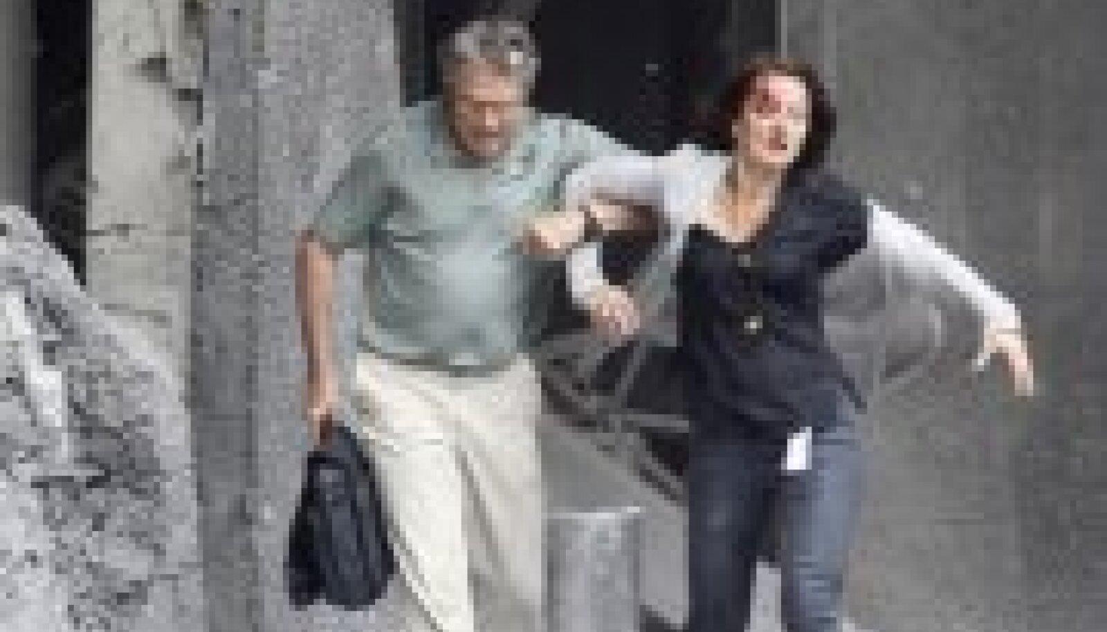 Mees aitab pärast pommiplahvatust Oslos vigastada saanud naisel majast väljuda