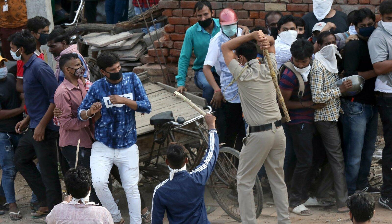 India politsei ajamas alkoholipoodide ette kogunenud rahvahulki laiali