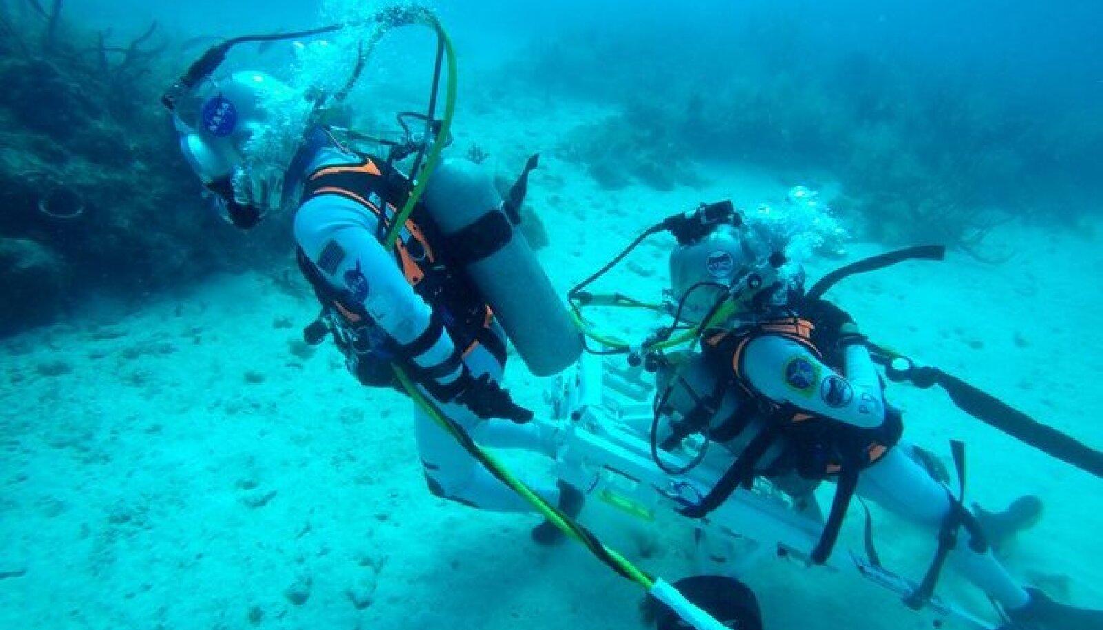 NASA astronaut Kjell Lindgren tirib ESA astronauti Pedro Duqued, kes lebab päästeseadmel, 20 m sügavusel mere põhjas. Merepõhi meenutab suurepäraselt Kuu pinnast, samuti on võimalik simuleerida vee all erineva tasemega raskusjõudu. Seetõttu oli viimane NEEMO missioon suurepärane koht Euroopa Kosmoseagentuuris Kuu-matkade jaoks välja töötatud varustuse testimiseks. Foto: NASA