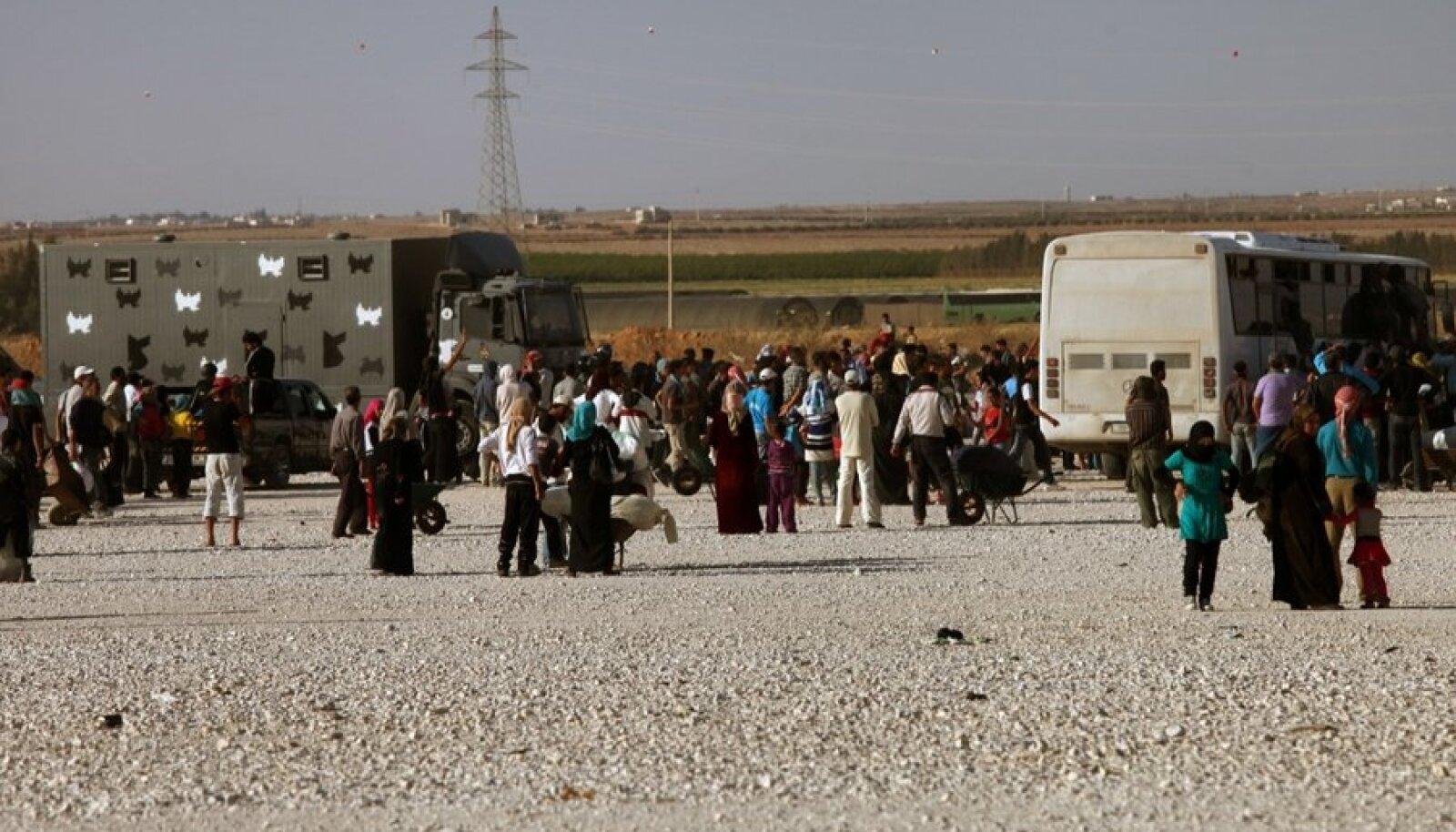 Süüria põgenikud ootavad sõjaväebussi Zaatari põgenikelaagrisse Süüria piiri ääres