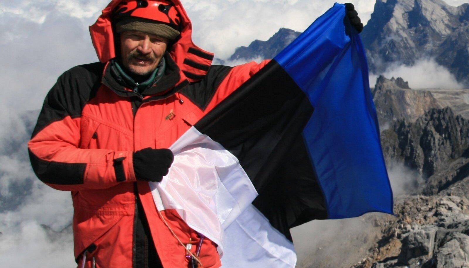 Tüüpiline lipuga mäetipupilt. Taamal olev Puncak Jaya ehk Carstenz Pyramid on Paapua Uus-Guinea kõrgeim mägi.