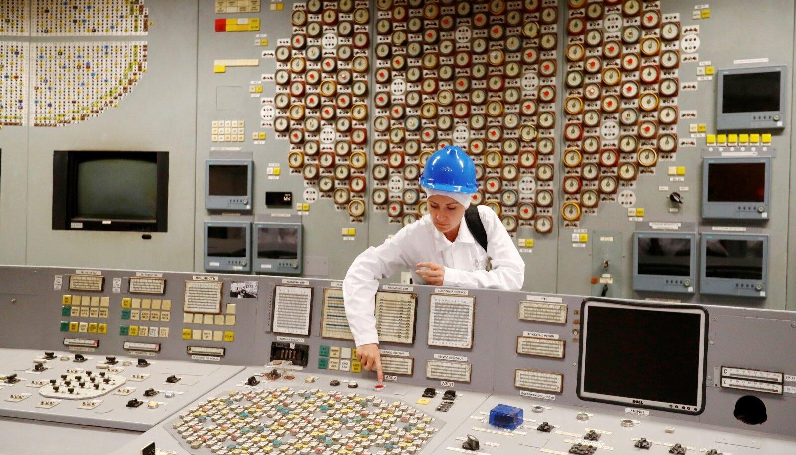 """PISIKE PUNANE NUPP: Giid näitab punast nuppu Ignalina tuumajaamas. Jaam muutus popiks turismiobjektiks pärast seda, kui HBO võttis seal üles menusarja """"Tšernobõl""""."""