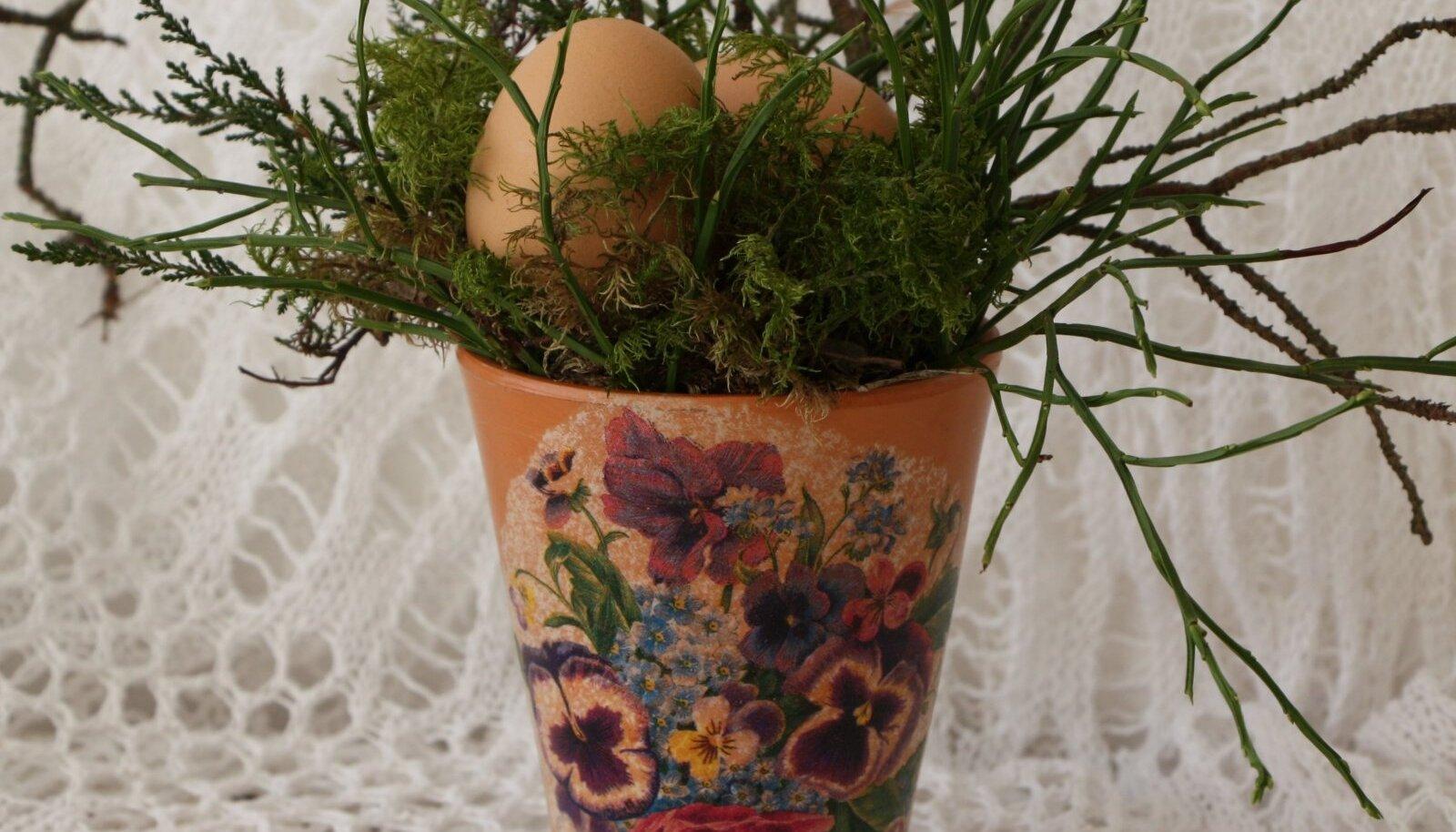 Vanale vaasile on kantud lilleline pilt. Pange vaasi pisut sammalt ja oksi ning sinna sisse peitke munad.