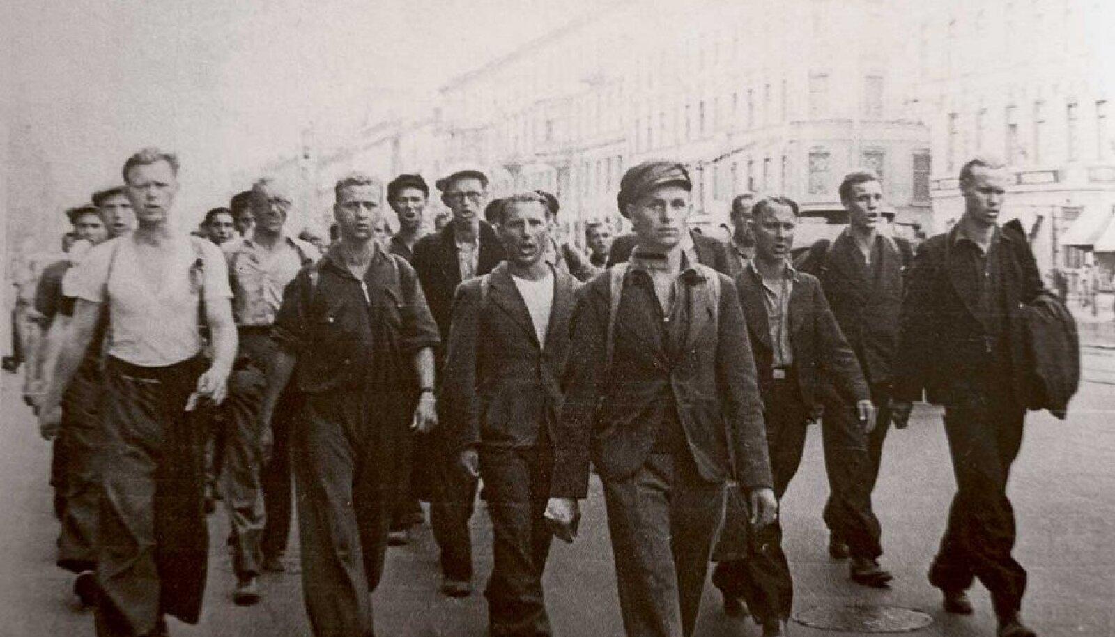 Surmalaagritesse: Sõtta mobiliseeritud eestlased sammumas Leningradi tänavatel. Need suveriietes mehed saadeti rinde asemel kaugele itta metsa langetama. Hukkus iga kolmas.