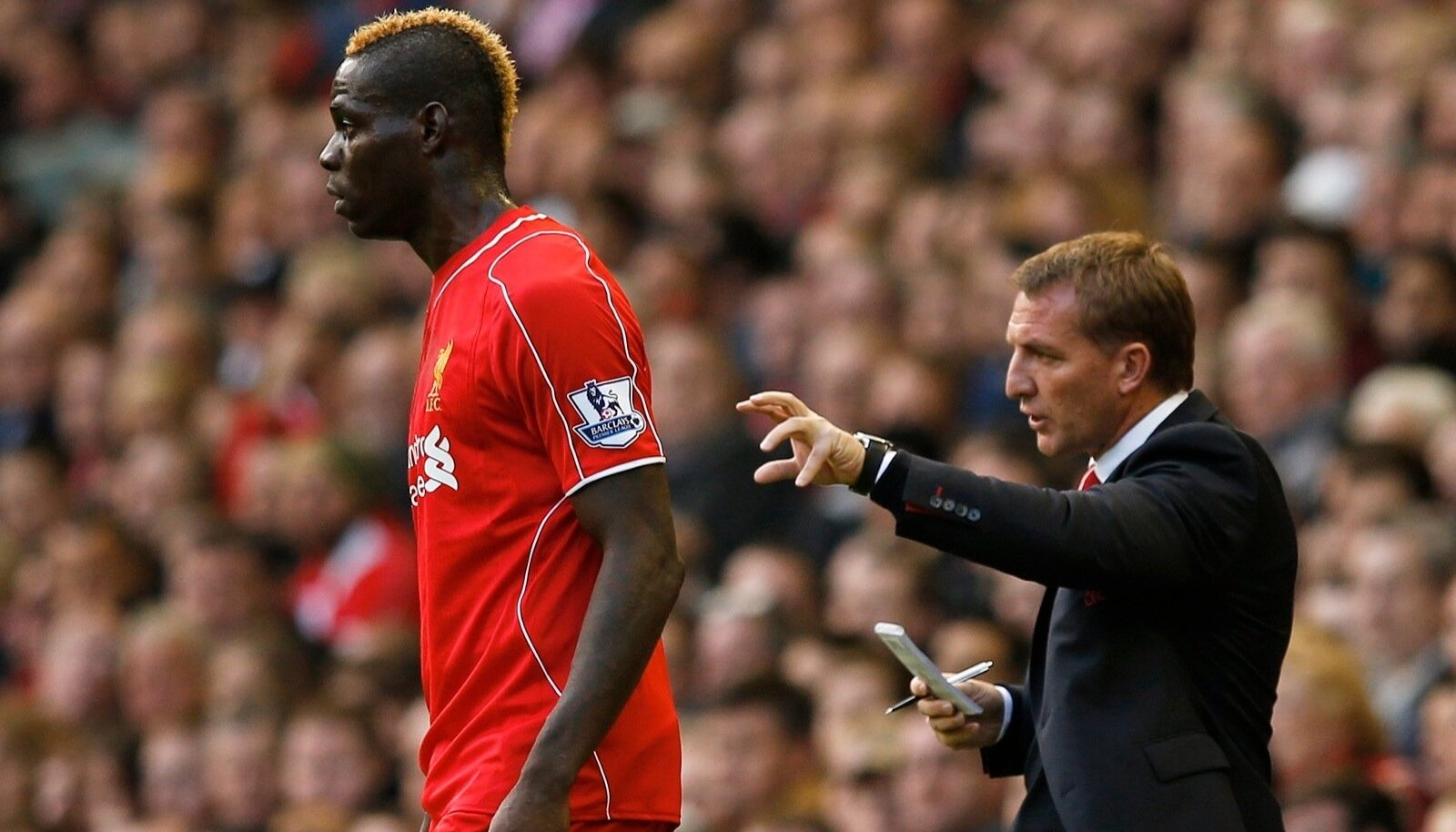 Liverpool's Mario Balotelli watches play as manager Brendan Rodgers gives instructions during their English Premier League soccer match against Hull City at Anfield in Liverpool
