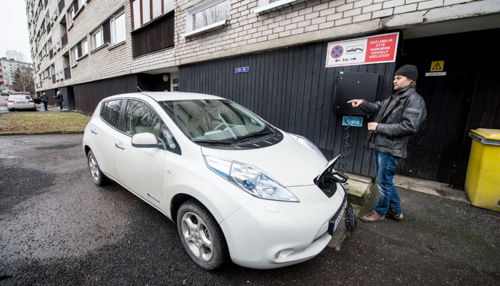 Glen Pilvre laeb oma elektriautot kortermaja külge pandud elektrikapist. Katlamaja ees ei tohi parkida tossavad sisepõlemismootoriga autod, kuid elektriauto endast ohtu ei kujuta.