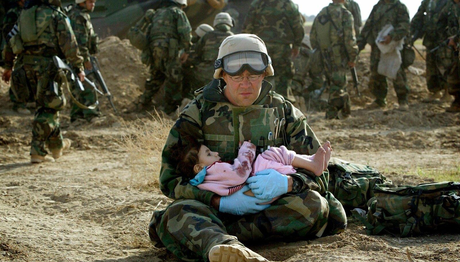 Iraagi sõda 2003. USA sõdur hoiab süles Iraagi last, kelle pere sai kahe tule vahel surma.