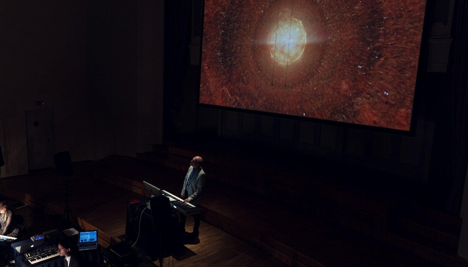 """SURMATÄHT: """"Hingus 2021"""", laval helilooja Sven Grünberg, ekraanil Tencu visuaal."""
