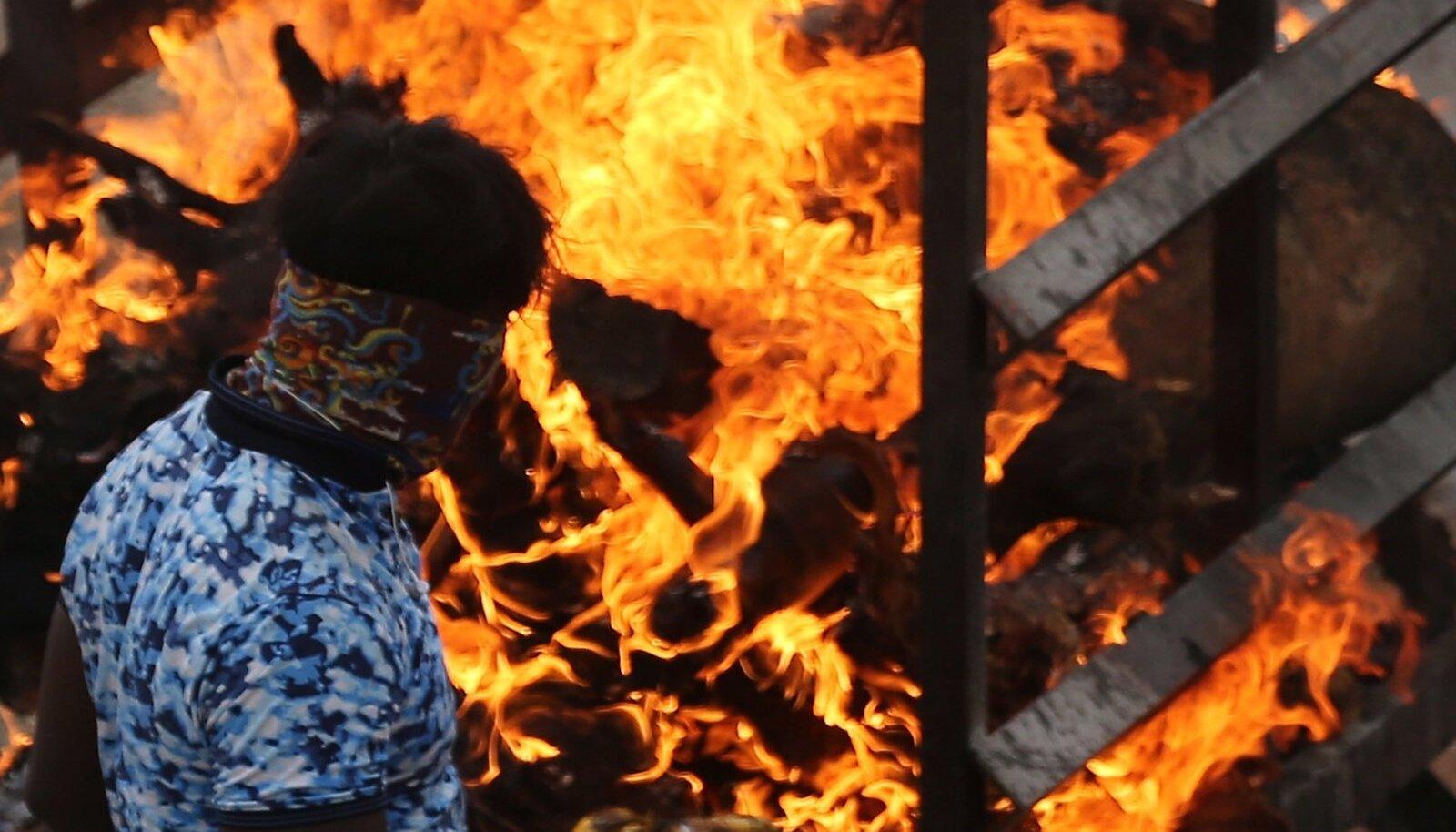 TULEMÖLL: Mees jälgib järjekordset põletusmatust Bangalore äärelinnas. Osades India linnades on krematooriumite päevane töömaht kasvanud võrreldes varasemaga kümnekordselt.