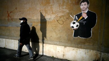 """LÄBIKUKKUNUD VÕIMUPÖÖRE: Mees kõndimas mööda Itaalia kunstniku Laika seinajoonistusest """"Il Golpe Fallito"""", millel kujutatakse jalgpalli tühjaks torkavat Torino Juventuse presidenti Andrea Agnellit. Juventus on üks uue superliiga idee eestvedajatest."""